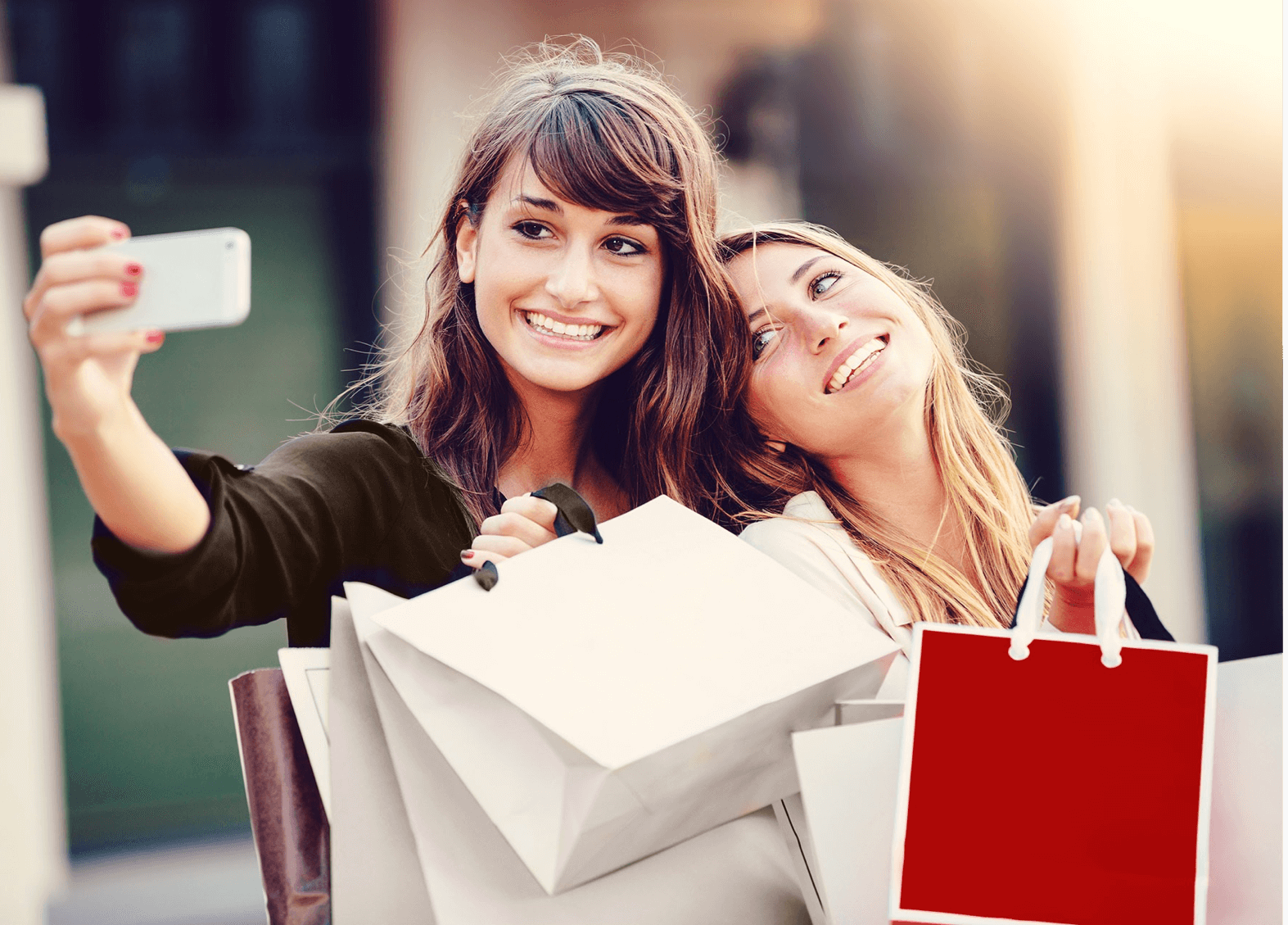 two girls taking a selfie with shopping bags